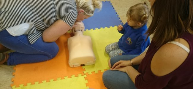 Mother learning CPR while little one looks on